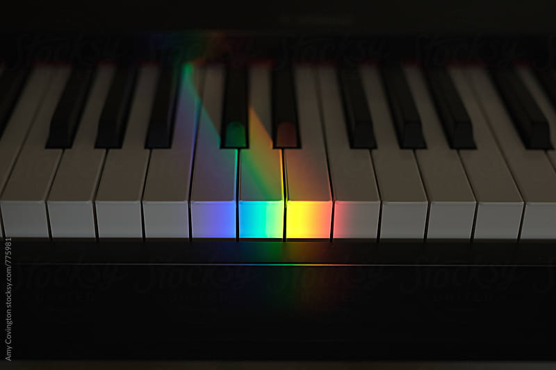 Rainbow ray of light on piano keys by Amy Covington for Stocksy United