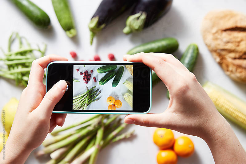 Person taking shot of raw vegetables and fruit by Martí Sans for Stocksy United
