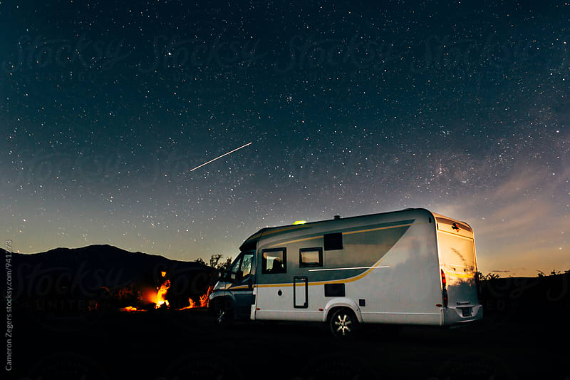 man by campfire near motorhome with night sky by Cameron Zegers for Stocksy United