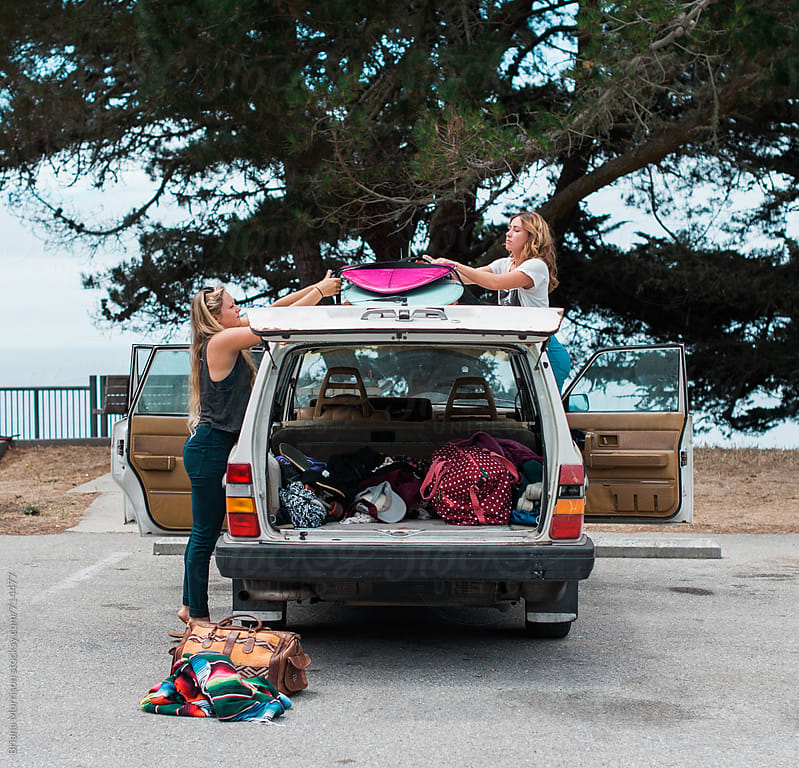 Two Women Unloading Surfboards from the Roof of Their Car by Briana Morrison for Stocksy United