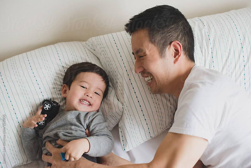 Dad tickling baby on bed by Lauren Naefe for Stocksy United