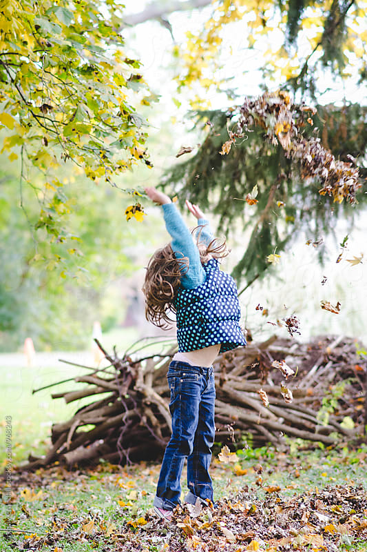 Child throwing leaves into the air during fall by Lindsay Crandall for Stocksy United