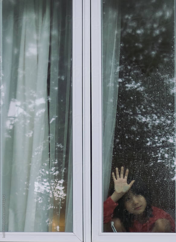 Young boy looks though rainy window by kelli kim for Stocksy United