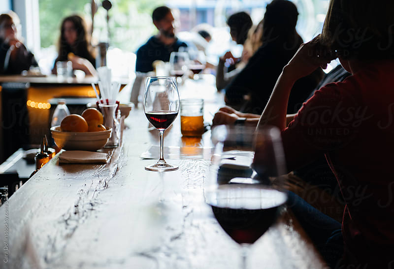 Glass of red wine on a bartop at a busy restaurant by Cara Dolan for Stocksy United