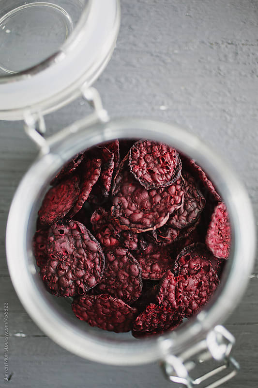 Beetroot chips: Closeup of an open jar of beetroot chips. by Darren Muir for Stocksy United