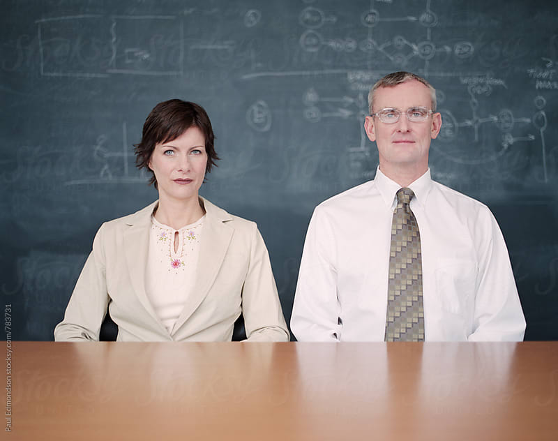 Portrait of male and female business executives sitting at boardroom desk by Paul Edmondson for Stocksy United