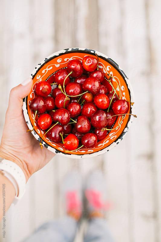 Woman holding cherries by Maja Topcagic for Stocksy United