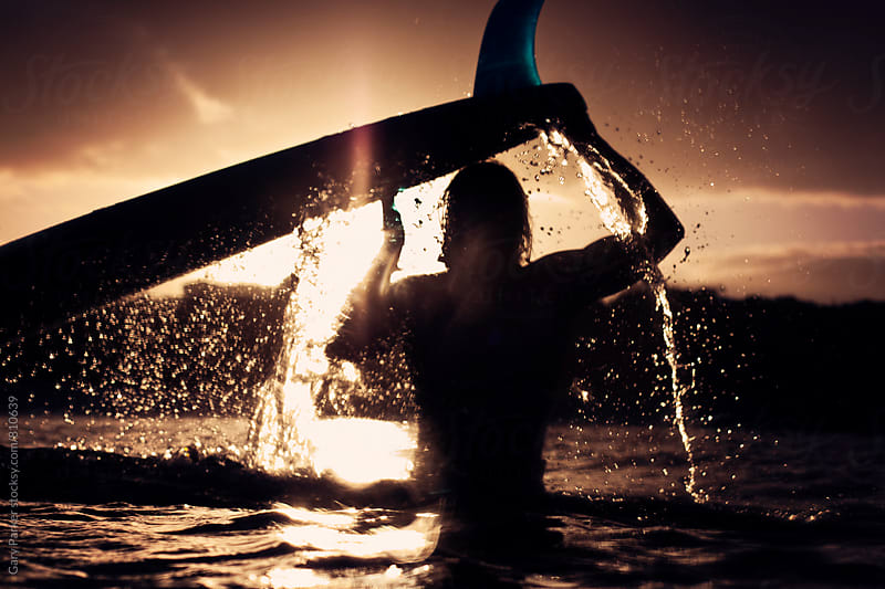 A silhouette of a man holding a surfboard over his head while the sun sets by Gary Parker for Stocksy United