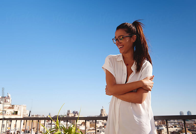Young smiling woman standing on balcony by Guille Faingold for Stocksy United