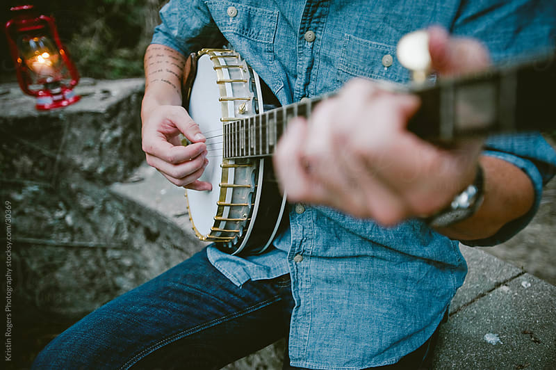 Man playing a banjo while camping in forest by Kristin Rogers Photography for Stocksy United