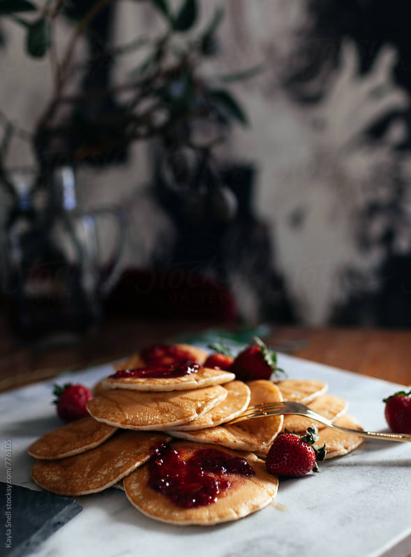 Pile of pancakes with jam and fruit by Kayla Snell for Stocksy United