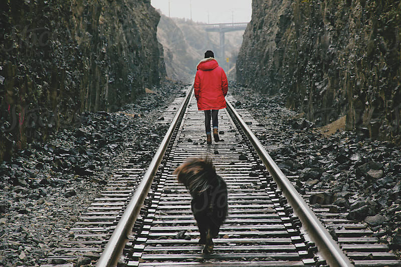 Dog follows woman walking on railroad tracks by Tari Gunstone for Stocksy United