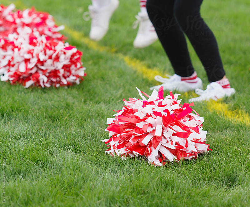 Cheerleading pom pom sits on grass of football field by Tana Teel for Stocksy United