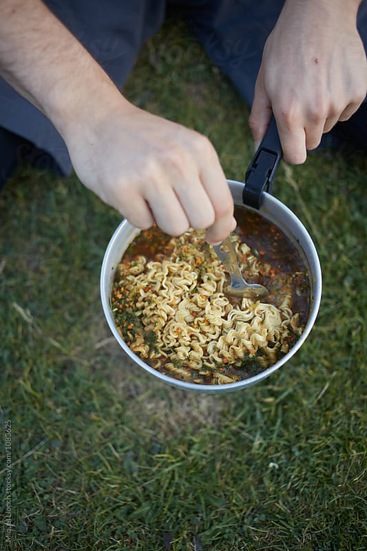 Backpacking cooking with noodles  by Miquel Llonch for Stocksy United