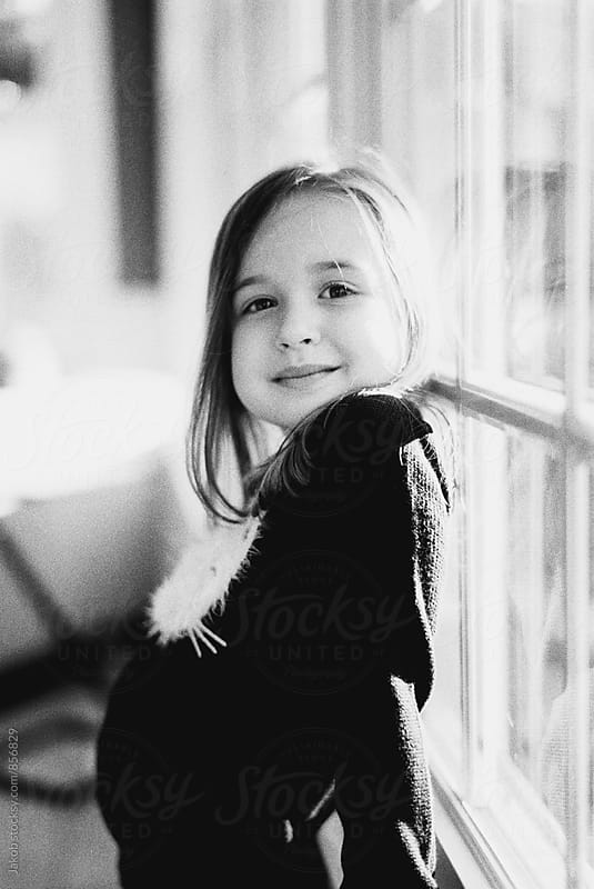 Black and white portrait of a beautiful young girl by a window by Jakob for Stocksy United