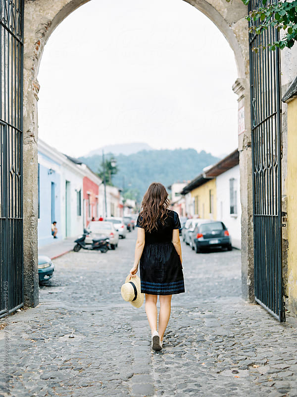 Woman walking down cobblestone street by Daniel Kim Photography for Stocksy United