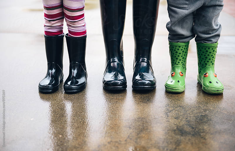 Just legs of mother, daughter and son standing outside wearing rainboots. by Emmanuel Hidalgo for Stocksy United