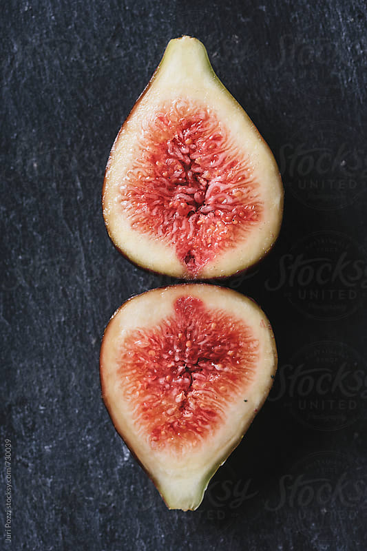 sliced figs on a black stone by Juri Pozzi for Stocksy United