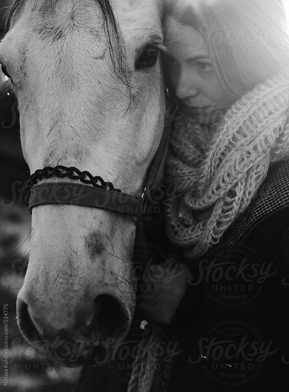 Woman and a horse holding their heads together by Natasa Kukic for Stocksy United