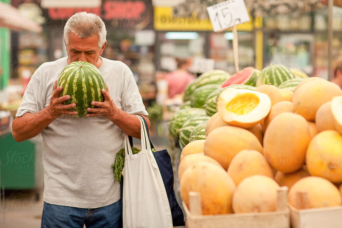 Old man buying fruits and vegetables at the local market. by ...