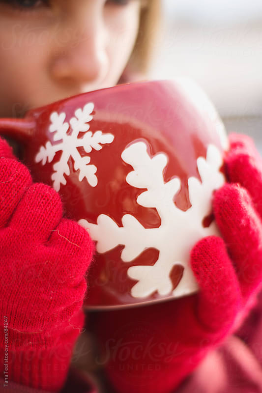 Girl wearing red gloves sips hot chocolate out of a red snowflake mug  by Tana Teel for Stocksy United