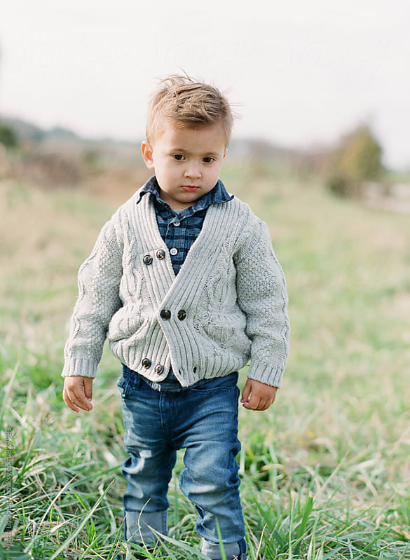 Boy in sweater in field by Marta Locklear for Stocksy United