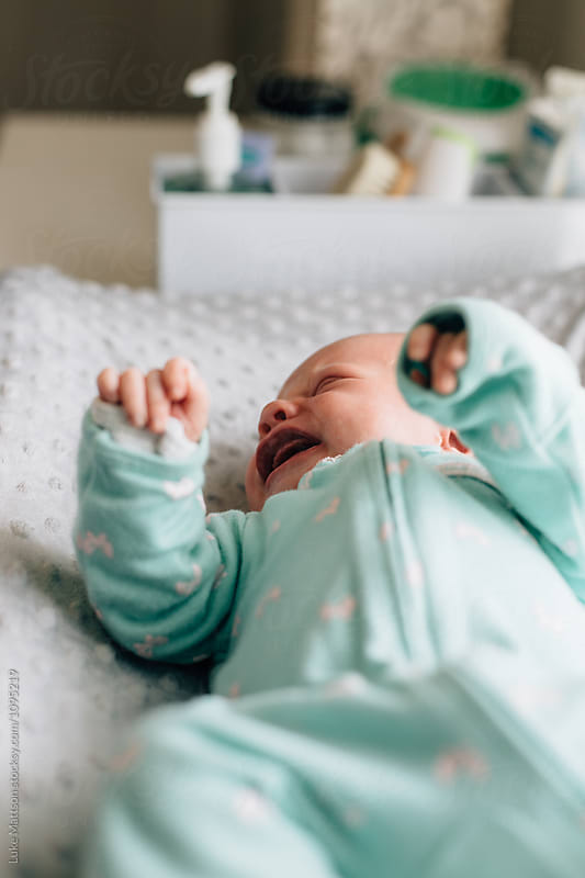 Newborn Baby Girl In Green Onesie Crying On Changing Table by Luke Mattson for Stocksy United
