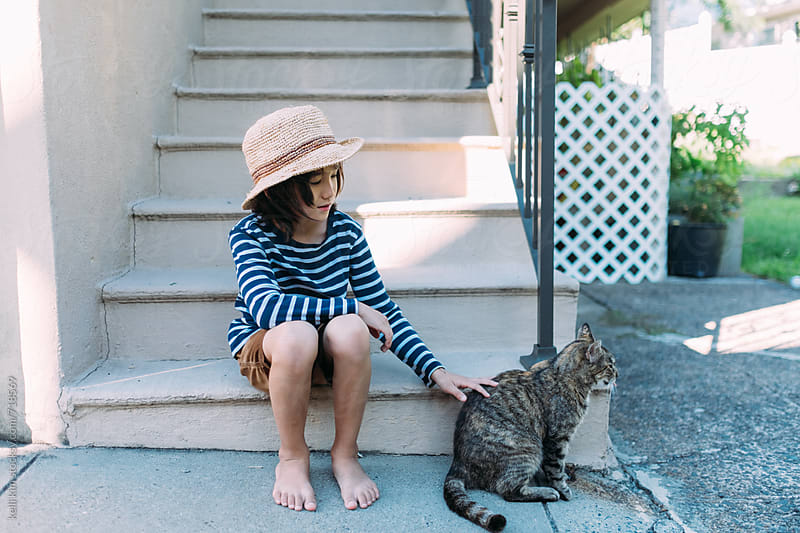 Young boy pets his outside cat by kelli kim for Stocksy United