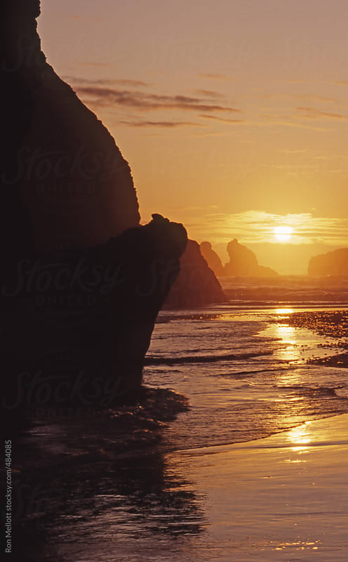 sunset behind seastacks on the southern coast of Oregon with incoming tide by Ron Mellott for Stocksy United