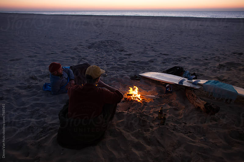 Two friends camping on the beach net to a bonfire  by Denni Van Huis for Stocksy United