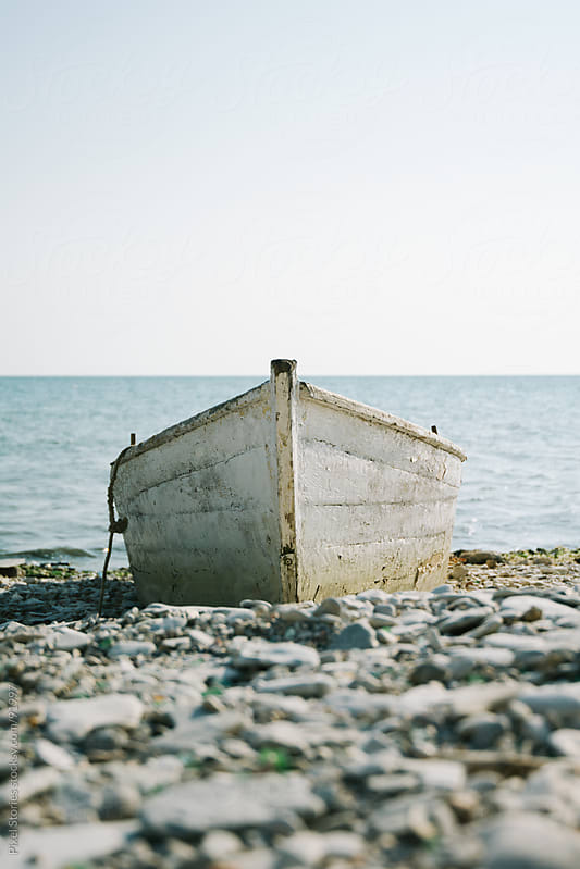 Old boat on seashore by Pixel Stories for Stocksy United