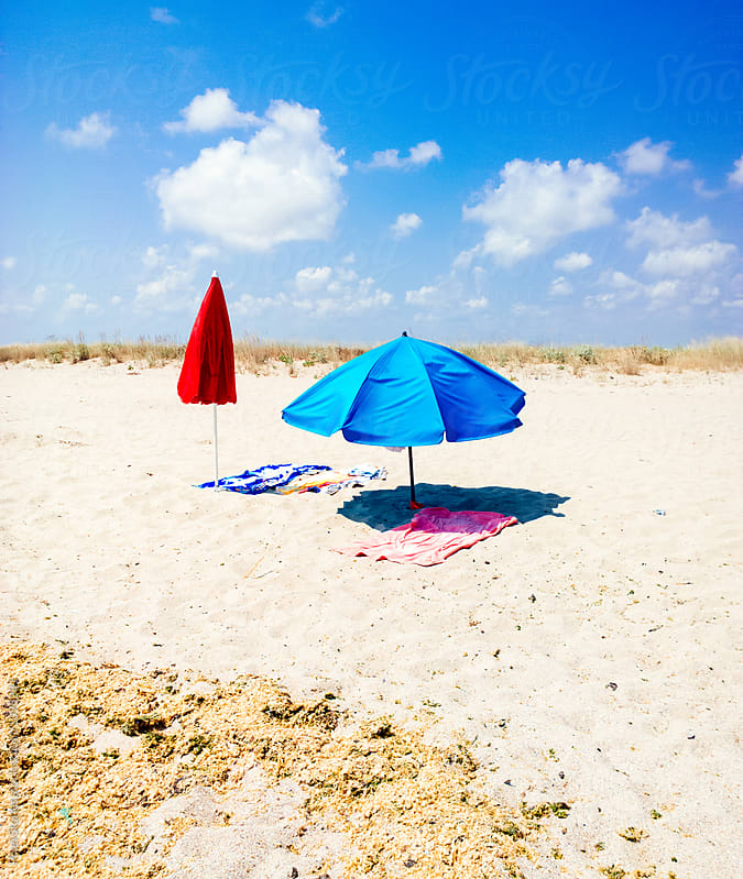 Two empty beach towels and umbrellas by Pixel Stories for Stocksy United