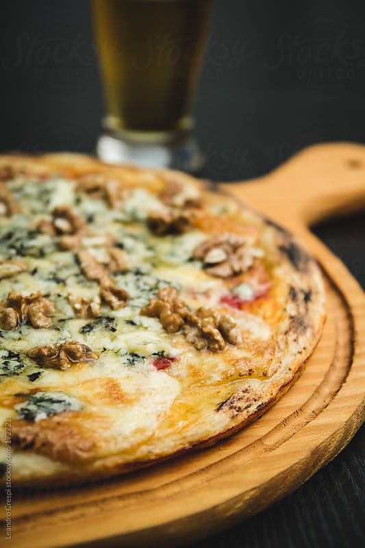 Pizza, Roquefort cheese and nuts, beer by Leandro Crespi for Stocksy United