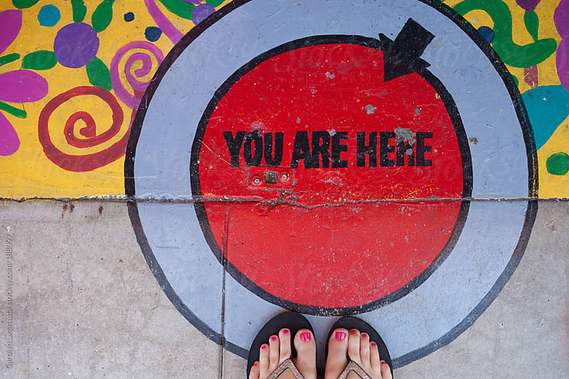 Feet in flip flops standing on a painted sidewalk that says: You are here by Carolyn Lagattuta for Stocksy United