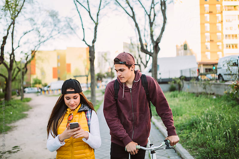 Teen Couple Walking and Looking at a Mobile Phone by Victor Torres for Stocksy United