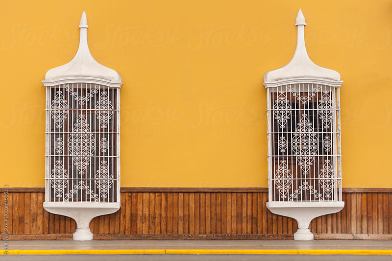 White Spanish colonial balconies on a rendered yellow and timber wall by Ben Ryan for Stocksy United