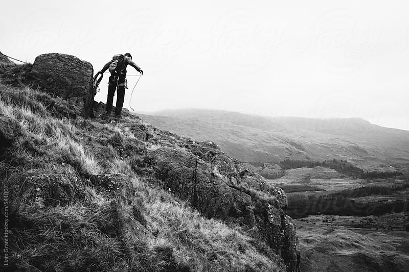 Mountaineer gathers rope on edge of mountainside.  by Liam Grant for Stocksy United