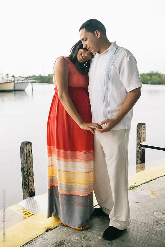 Happy Pregnant Couple on Pier by Stephen Morris for Stocksy United