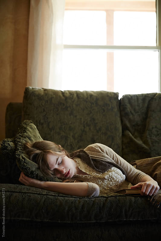 Woman sleeping on sofa in living room by Trinette Reed for Stocksy United