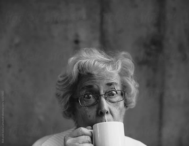 Funny portrait of senior caucasian woman hiding behind coffee mug by Rob and Julia Campbell for Stocksy United