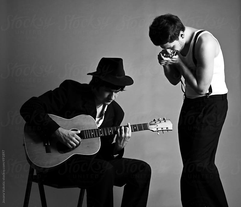 Two men playing instruments by Jovana Vukotic for Stocksy United
