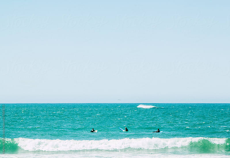 Three surfers waiting for their wave to ride by Naoko Kakuta for Stocksy United