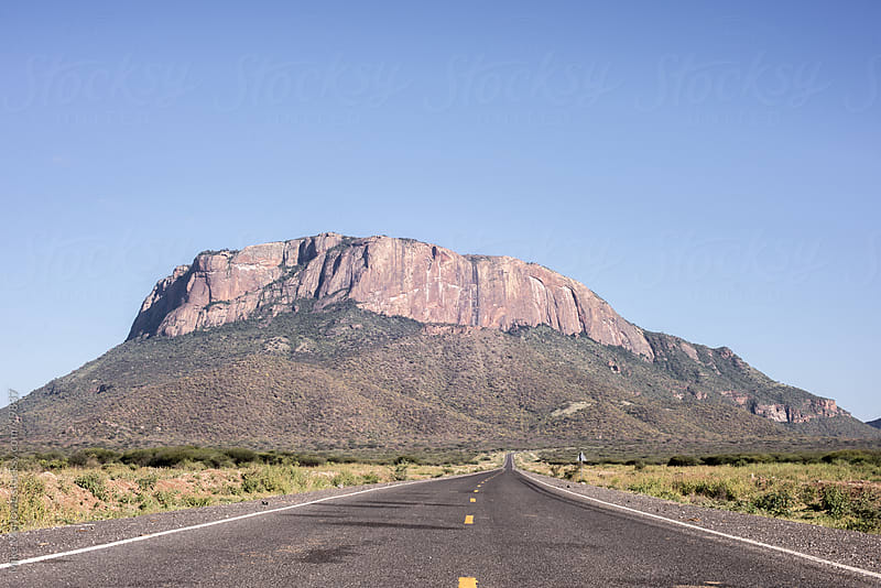 Shot of an open road leading in to the distance with a hill on the horizon. by Mike Marlowe for Stocksy United