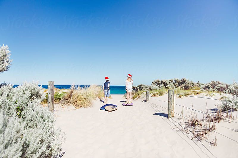 Two children walking through sand dunes to the beach on Christmas Day in Australia by Angela Lumsden for Stocksy United