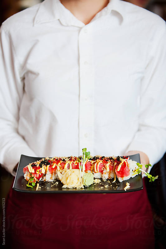 Sushi: Server Holding Spicy Tuna Roll by Sean Locke for Stocksy United