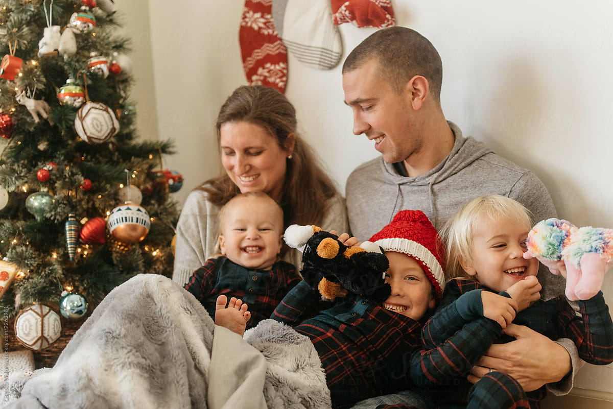 A family sitting by the christmas tree and relaxing by Chelsea Victoria -  Stocksy United