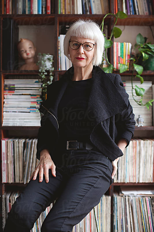 Stylish older woman indoors in front of books and records by Natalie JEFFCOTT for Stocksy United
