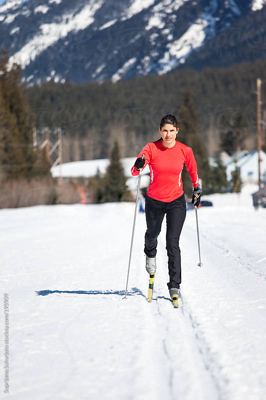 Female skier cross-country skiing on a sunny winter day by Suprijono Suharjoto for Stocksy United