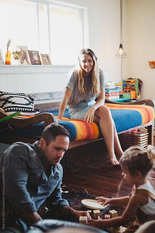 Mom watching cute young toddler girl and dad playing with building blocks inside by Rob and Julia Campbell for Stocksy United