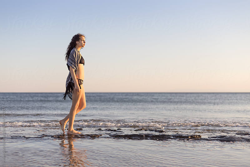 Young Woman Walks on a Rocky Shore by Helen Sotiriadis for Stocksy United